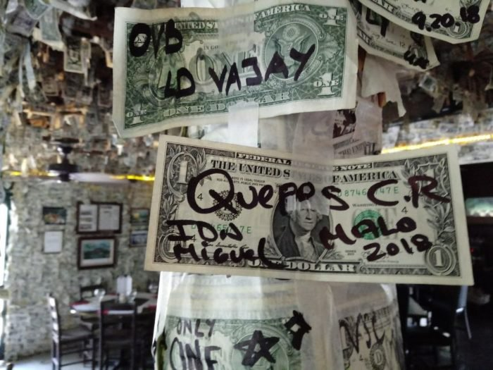 close up of autographed dollar bills on taped to beam