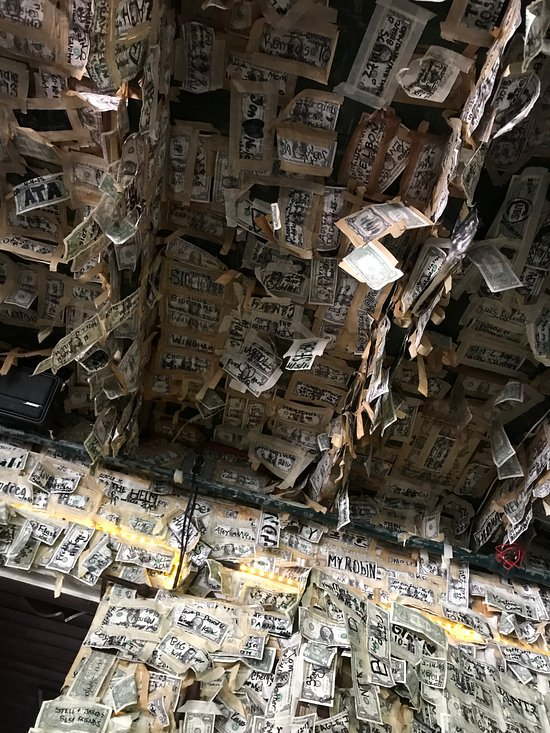 many, many dollar bills taped to ceiling and walls