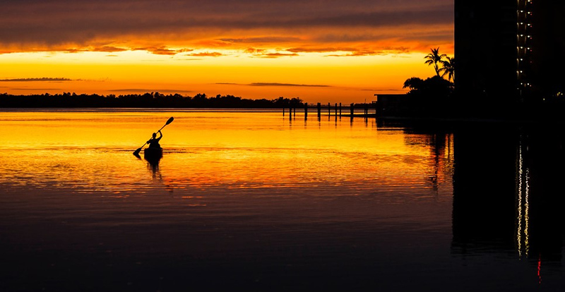 kayaker in the water at sunste