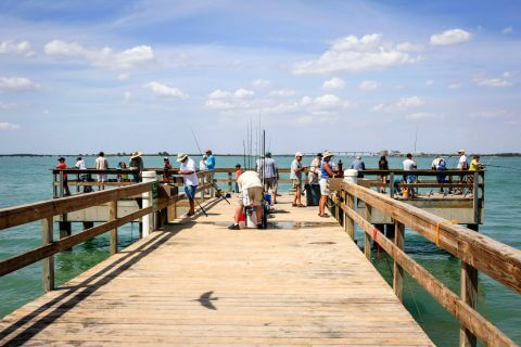 Looking down the pier at people fishing on Sanibel Island